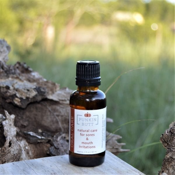 Image of a small bottle of Punkin Butt Natural Oral Care Oil on a wooden table set in a green field.